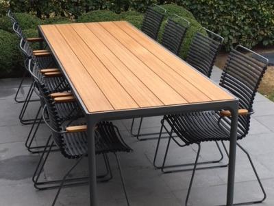 Tuintafel met 8 tuinstoelen met houten armleuningen met tuintafel op terras met betontegels